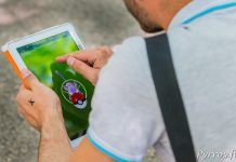 Un dresseur de pokemon lance une pokéball sur un Rattata dans l'application Pokemon Go