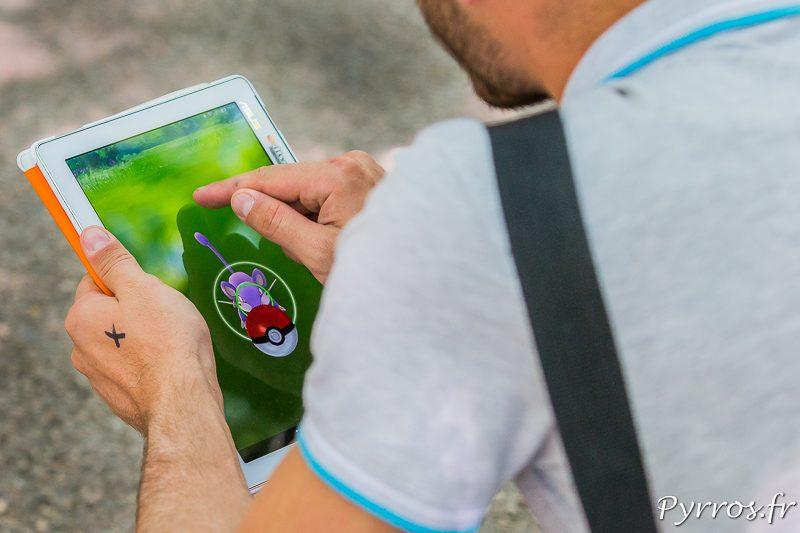 Un dresseur de pokemon lance une pokéball sur un Rattata dans l'application Pokemon Go