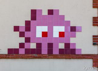 Un invader est posé sur le mur d'un batiment de Toulouse, il regarde passer les trains (TLS_10)