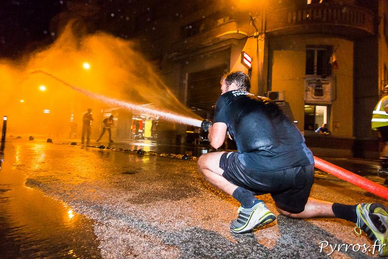 Un pompier arrose les patineurs qui sont surpris par le nombre des lances à incendie