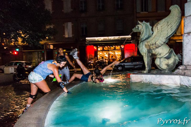 Une patineuse remplit son arme tandis qu'une autre tombe dans la fontaine