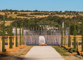 Une stèle commémorative est installée devant un monument