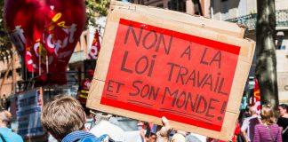 """Un manifestant porte une pancarte sur laquelle il est possible de lire """"Non à la loi travail et son monde"""""""