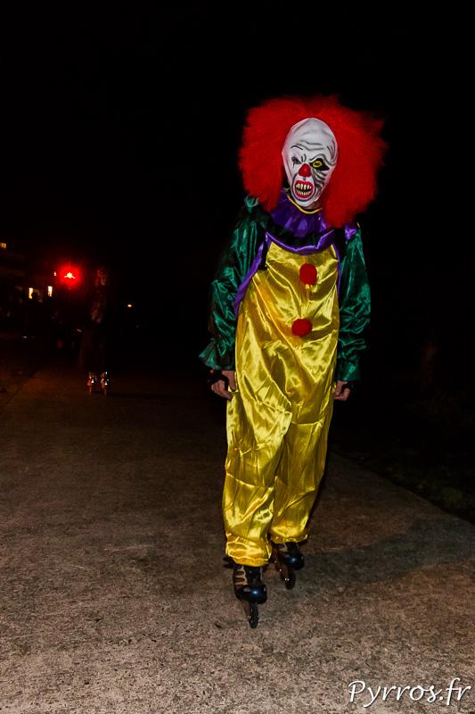 En roller, un clown effrayant surgit au mileiu des patineurs de la rando Halloween