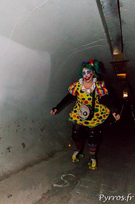 Dans un tunnel éclairé à la bougie electronique passe un clown
