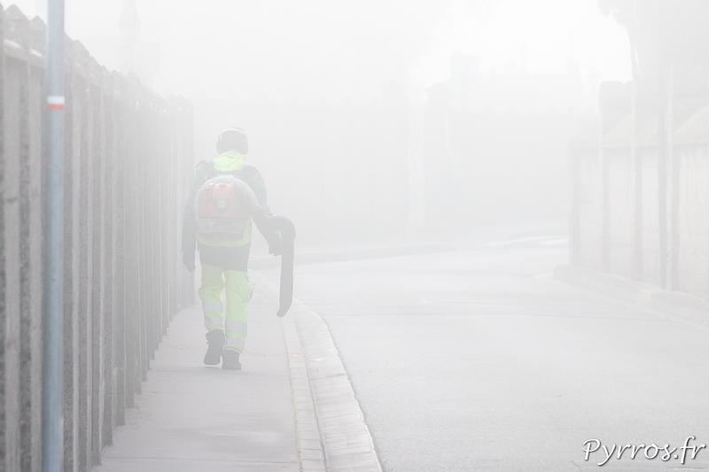Dans le brouillard matinal un employé municipale nétoie les abords du cimetière