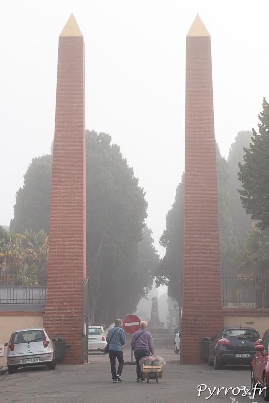 Armée d'une charrette un couple passe la porte principale du cimetière de Terre Cabade