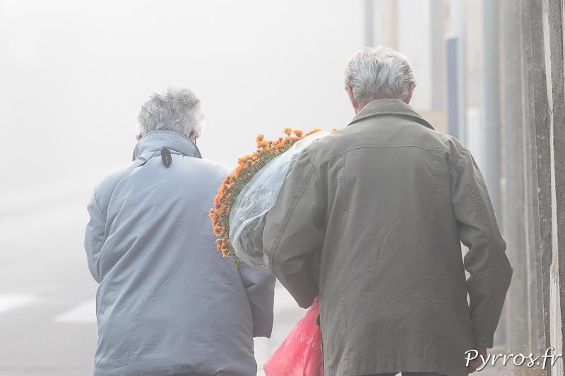 Un couple va fleurir la sépulture d'un proche au cimetière de Terre Cabade