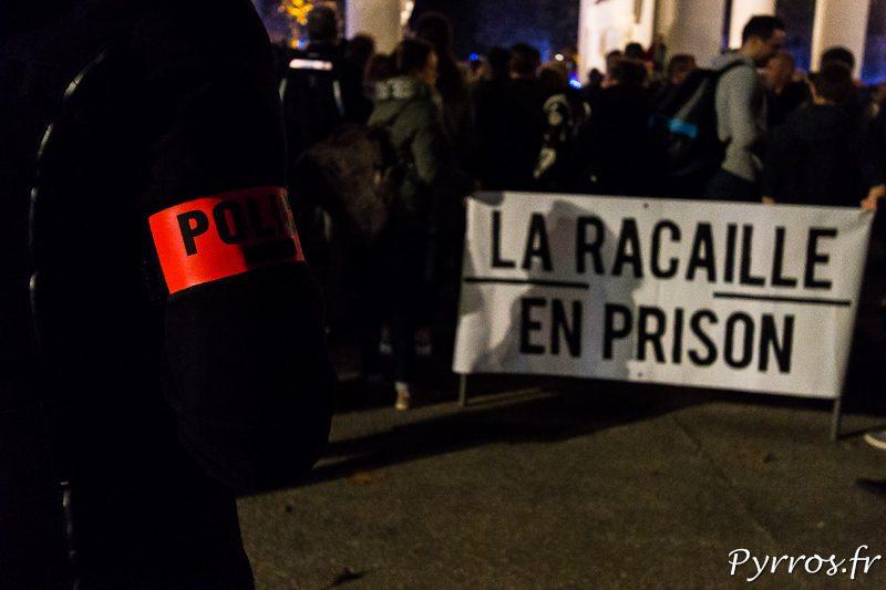 """Un policier regarde une banderole """"La Racaille en Prison"""""""