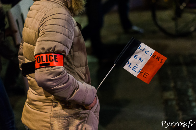 Une policière manifeste avec un drapeau tricolor sur lequel on lit Policiers en colère