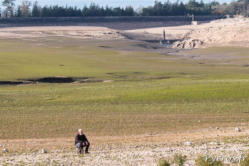 Vidange du lac de Saint Ferréol, un homme regarde le temps qui passe assis sur une pierre