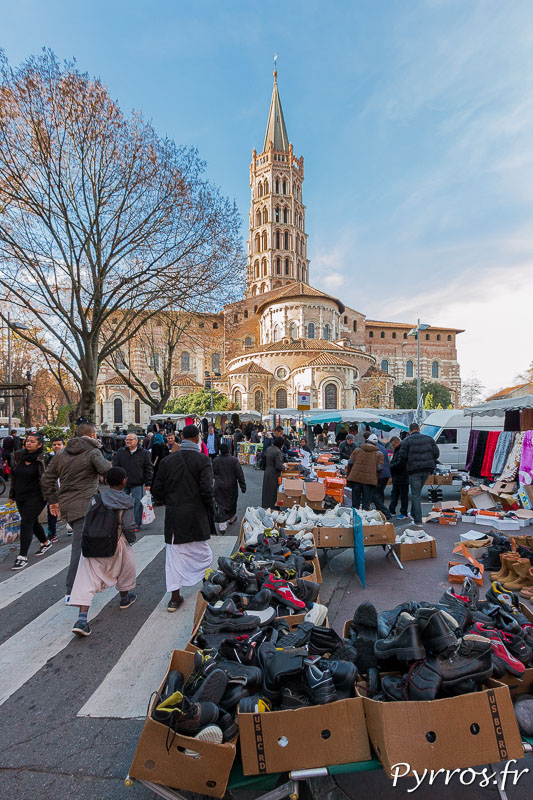Des chaussures débordent des cartons d'un commercant ambulant du Marché Saint Sernin