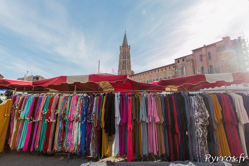 Des portants sont pleins de robes de chambre colorée au pied de la Basilique Saint Sernin