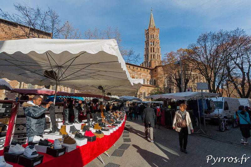 Dans les allées du Marché Saint Sernin de Toulouse une femme regarde des chaussures tandis que le vendeur range une paire de bottes