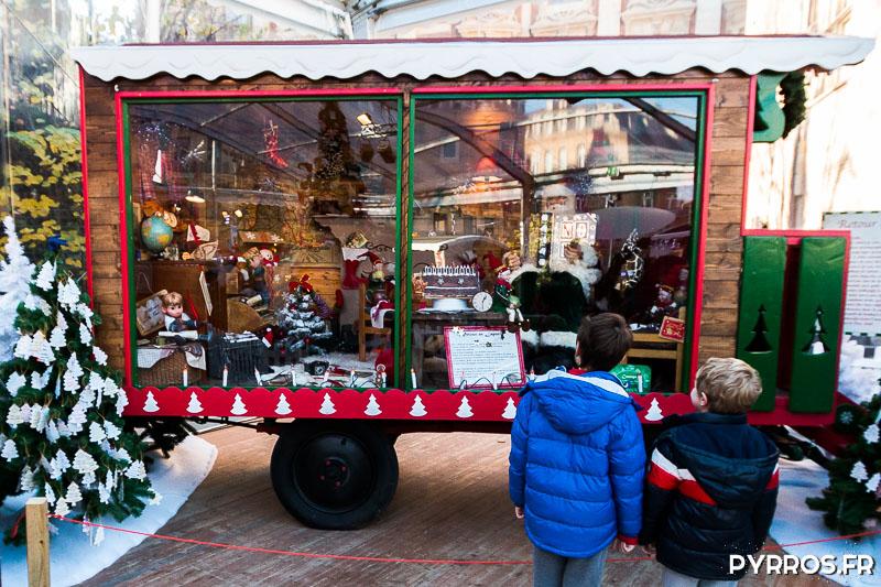 Deux enfants observent l'intérieur d'une roulotte qui raconte les souvenirs de voyages du Père Noël