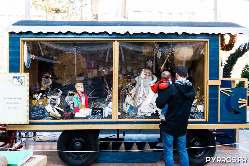 Un papa porte son fils pour qu'il regarde dans une roulotte qui raconte le voyage du Père Noël dans l'espace