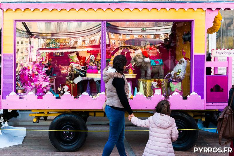 Une fille tient la main de sa maman. Elles observent la roulottes qui raconte les souvenirs du Père Noël en Inde