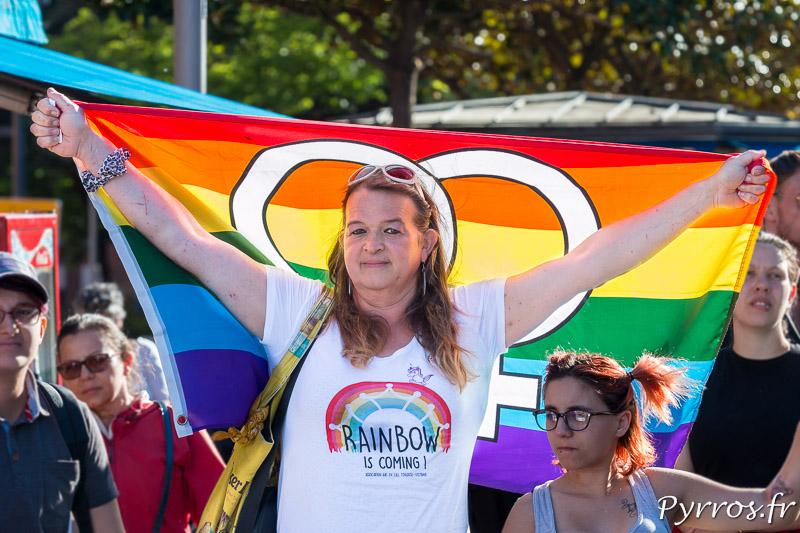 Une personne tend le drapeau du mouvement LGBT, le drapeau Arc en Ciel