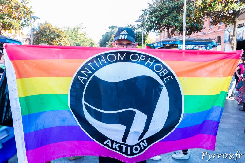 Une personne se cache derrière un drapeau contre l'homophobie