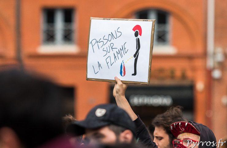 """Au dessus des manifestants surgit une affiche """"Pissons sur la flamme"""", le logo du Front National"""