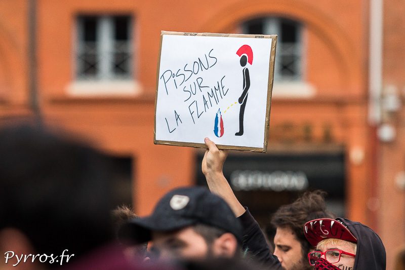 """Au dessus des manifestant surgit une affiche """"Pissons sur la flamme"""", le logo du Front National"""