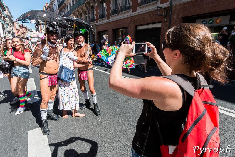 Un personne prend en photo son ami qui pose avec 2 personnes en tenue très légère