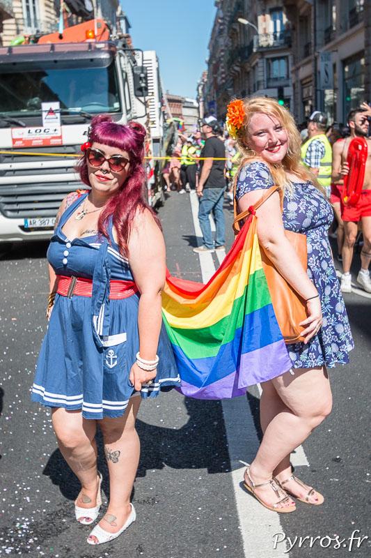 Deux jeunes femmes sont reliées par le drapeaux Arc en Ciel