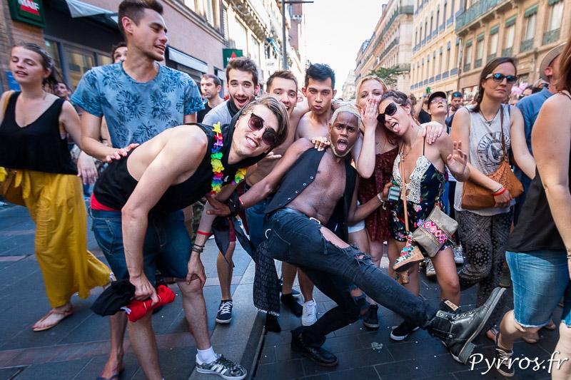 Un groupe de participants à la Marche des Fiertés de Toulouse posent en souriant devant l'objectif