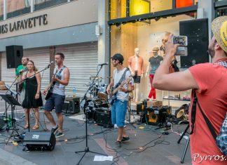 Un homme film avec son smartphone un groupe pop rock qui s'est installé devant les Galeries Lafayette