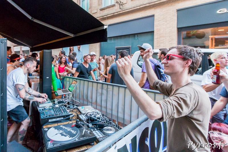 Un homme est emporté par la musique electro mixée par un DJ