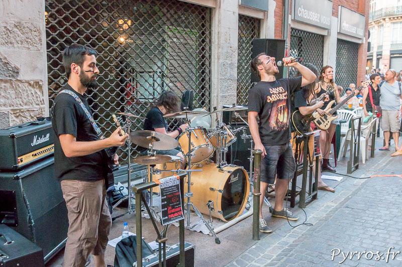 Un groupe de métal à pris place devant un bar dans une rue étroiteUn groupe de métal à pris place devant un bar dans une rue étroite