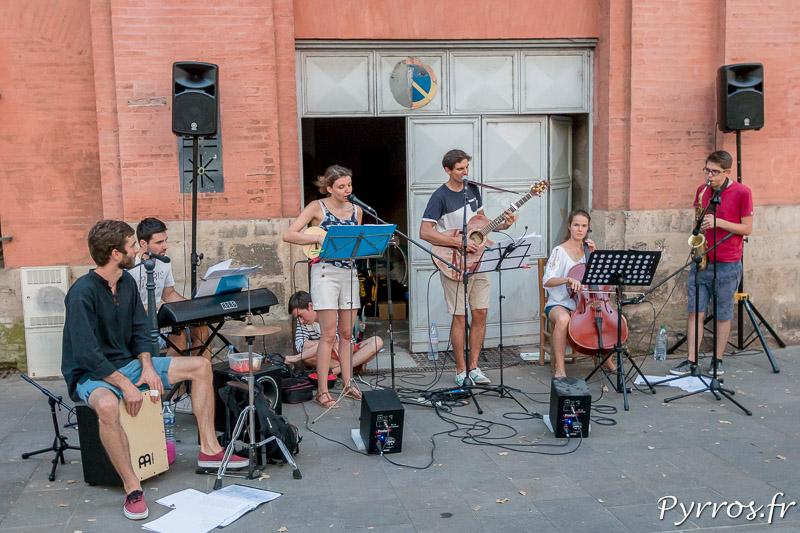 Un groupe de jeunes musiciens s'est installé devant un garage