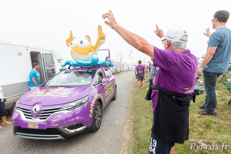 Génération Pèche passe devant un supporter habillé d'un tee shirt de ce partenaire du Tour de France