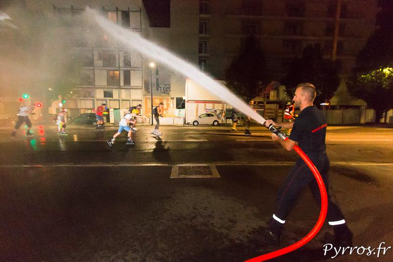 Un pompier de la Caserne Vion arrose les patineurs
