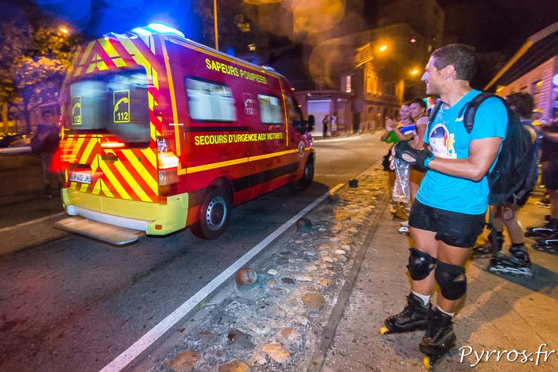 Un véhicule d'urgence part en intervention sous les applaudissements des patineurs