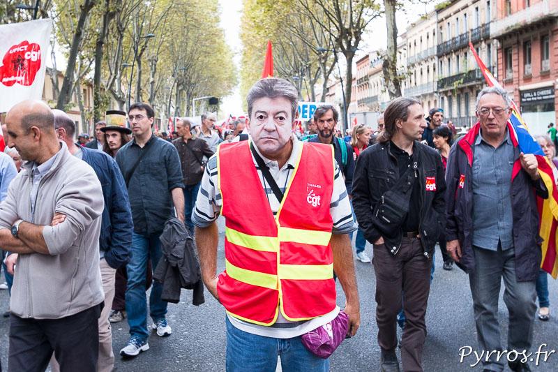 Un manifestant porte un masque de Jean Luc Mélenchon