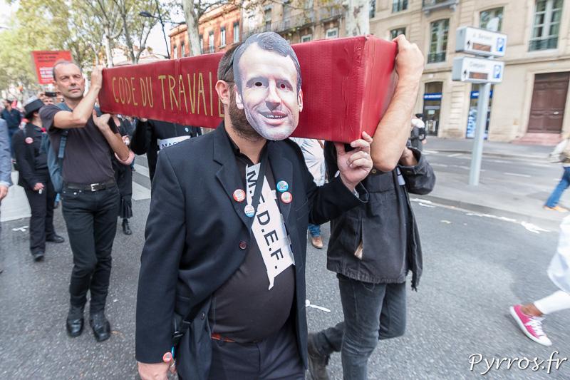Un manifestant porte un masque d'Emmanuelle Macron et porte le cercueil du Code du Travail