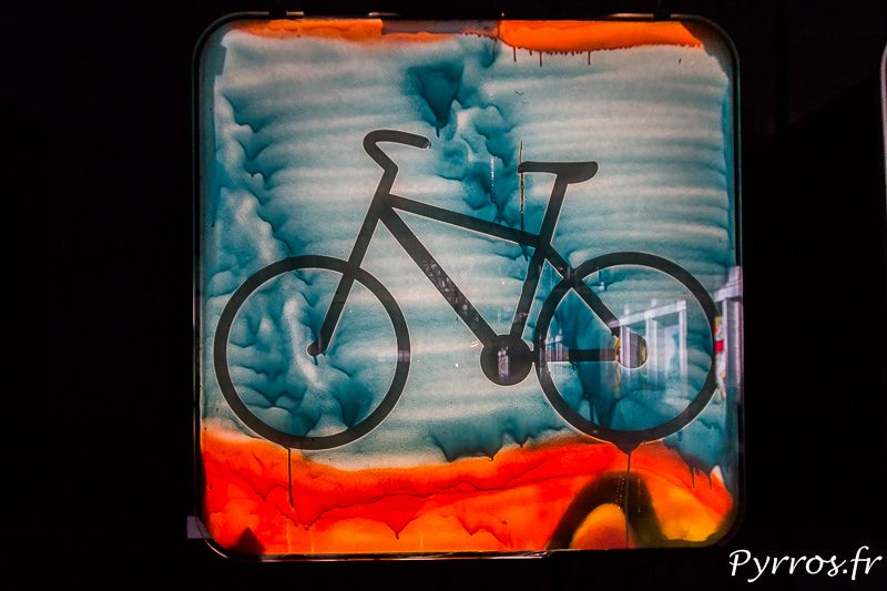 Dans un coin un artiste expose des vitres de train qui ont été graffées