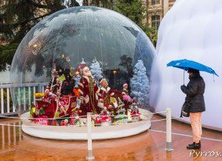 Sous la pluie une personnes observe une scene de vie du Père Noël