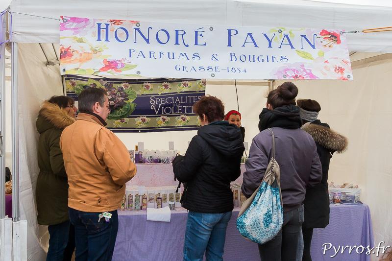 Un commerçant propose des parfums et bougies à la violette
