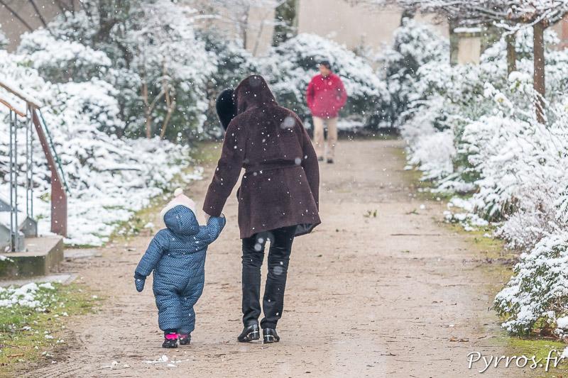 un enfant très emmitouflé dans sa combinaison est accompagné par sa nourice dans le Parc de l'observatoire