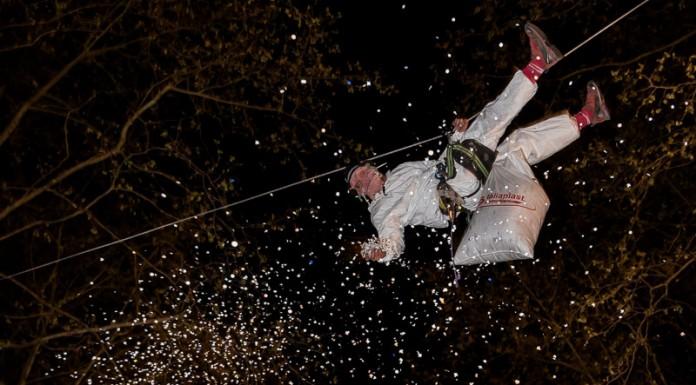 Dans le ciel au dessus des carnavaliers toulousains des hommes sont suspendu pour lancer une pluie de confettis