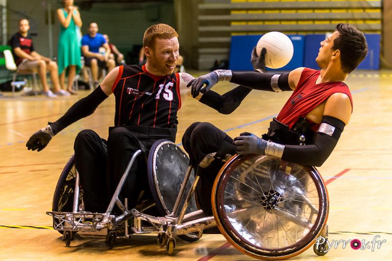 Alan LYNCH (15) de STADE TOULOUSAIN RUGBY HANDISPORT (France) passe le ballon en évitant les bras de Pieter DEN ADMIRANT (9) de AMSTERDAM PUSHERMEN (Pays-Bas)