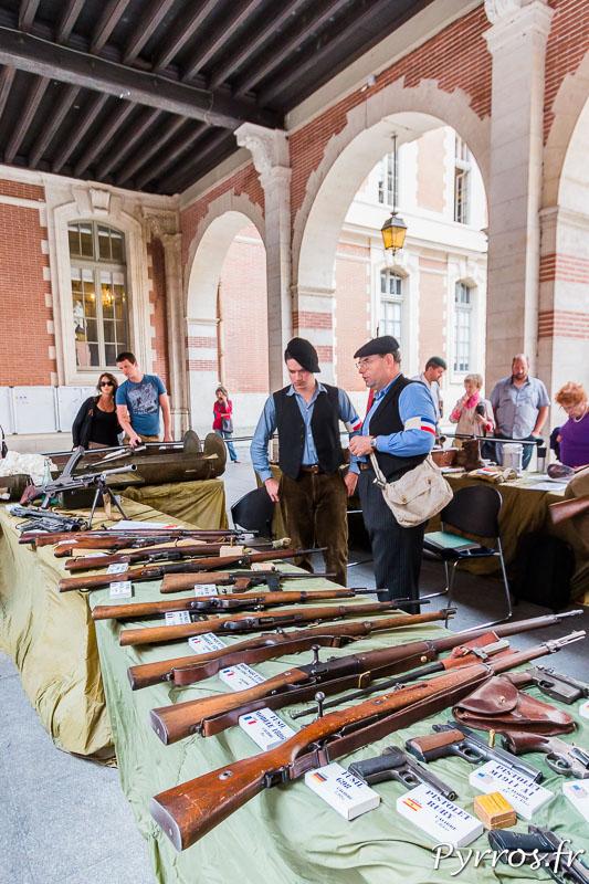 Dans la cour du Capitole sont exposées des armes et munitions utilisées par les maquis, ici des fusils et autres revolvers