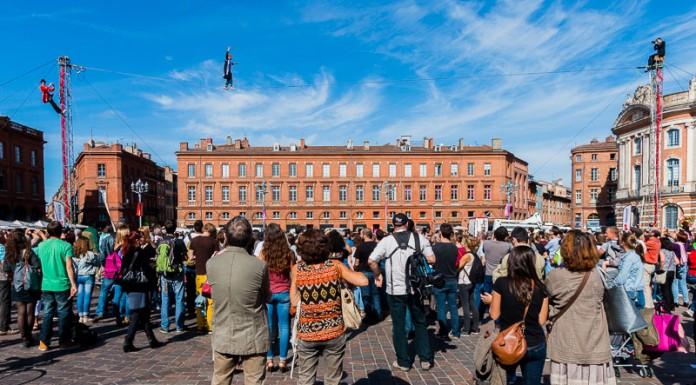 Le curé traverse la place du Capitole au dessus de la foule