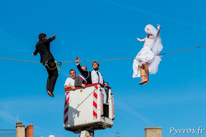 Le curé depuis une nacelle béni les jeunes mariés qui sont assis sur la slackline