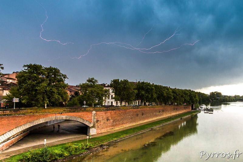 Un éclair rampant (Spider) illumine le ciel de Toulouse, des personnes s'abritent sous le pont de Garonette