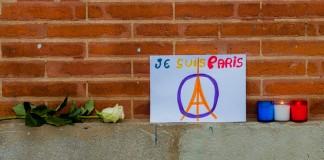 Une rose une affiche et des bougies déposées pour rendre hommage aux victimes des attaques terroristes