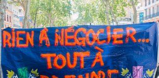 """Derrière une épaisse banderole sur laquelle on peut lire """"Rien à négocier tout à prendre"""" se cachent des manifestants cagoulés"""