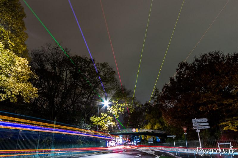 Au dessus de la frénésie routière les lasers de Starship par Yvette Mattern illuminent le ciel toulousain